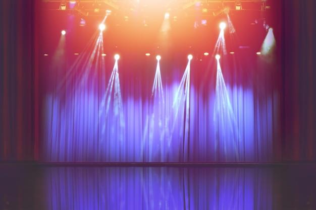 재미있는 다채로운 스포트라이트, 콘서트 조명의 추상적 이미지가 있는 흐릿한 빈 극장 무대