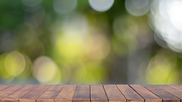 Blurred empty wooden table top with bokeh, blurred natural green background.
