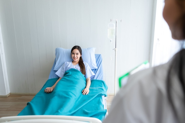 Blurred of female doctor therapeutic advising with positive emotions to a smile asian young female patient on bed in hospital background