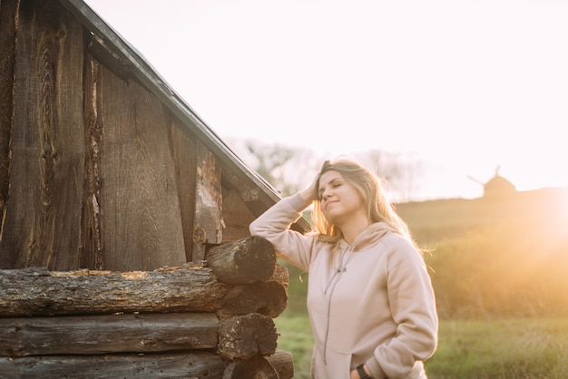 Blurred girl in a delicate pink sweater stands near a wooden old house and smiles