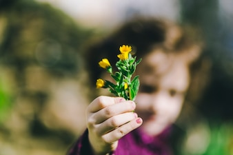 Blurred girl showing wild flowers