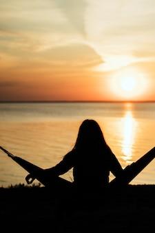 海の近くの崖の端にある松林のハンモックに座って、日の出を見てぼやけている女の子。