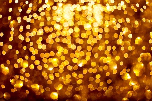黒の背景にぼやけた金色のライトあなたのデザインのためのお祝いのパターン