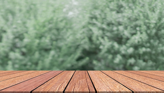 Blurred green leave with wood table background