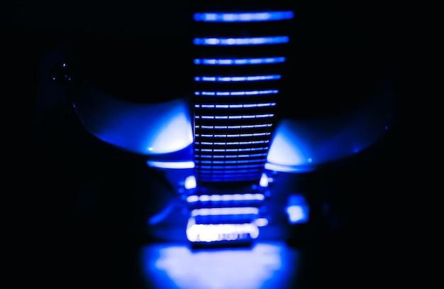ぼやけたギターの背景。楽器のネックと指板。明るい影のクリエイティブなスタイル。