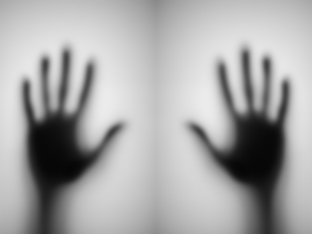 Blurred of a hand behind matted glass.