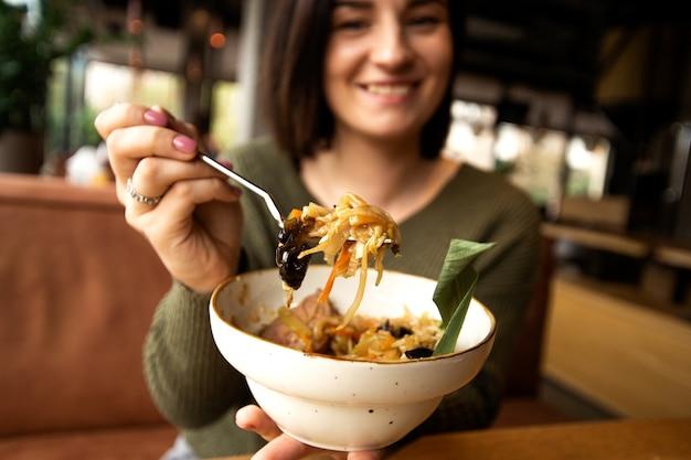 彼女のおいしい食事を見せて、笑顔でぼやけた幸せな女性。アジア料理のコンセプト。