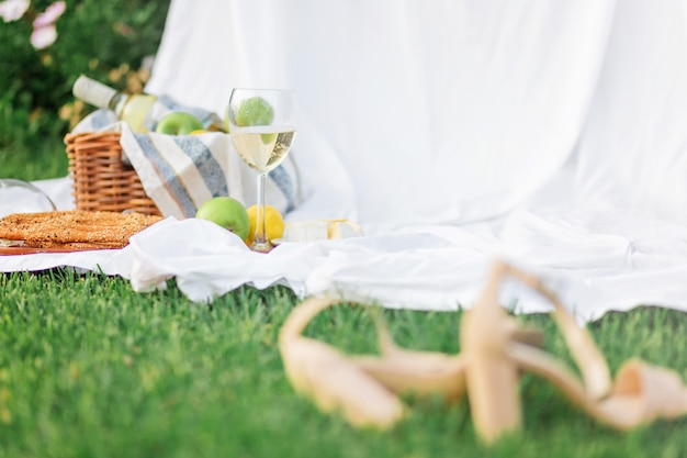 ぼやけたハイヒールの靴は、ピクニック用のセットが付いた籐のバスケットの横にありました。緑の草と白いシーツに。