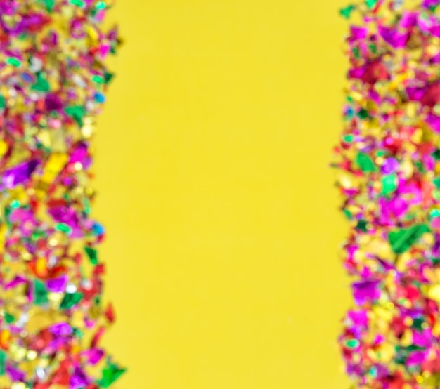 Blurred holidays background. colorful confetti decoration on yellow