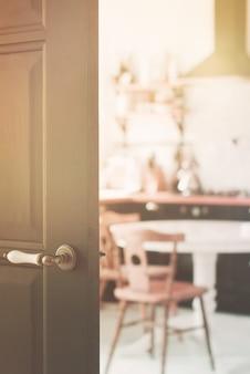 Blurred of home kitchen behind black wooden door