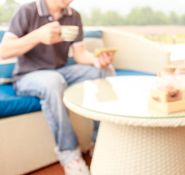 Blurred image of asian man is holding a cup of hot coffee and use his mobile phone.defocused image for background.