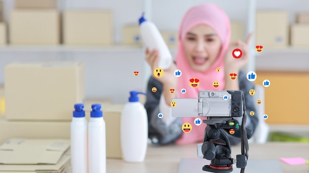 Blurred image of blogger asian muslim woman talking on video shooting with social media interaction, notification icons, wow, like, love, and smile. lifestyle with technology (focus on camera)