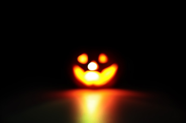 Blurred image of halloween pumpkin on black with dark filter