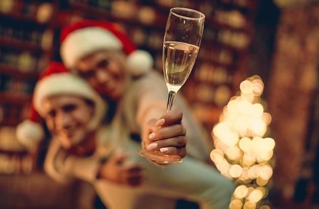 Размытое изображение влюбленной пары, испытывающей счастье от своего романа, проводящего вместе рождество или новый год. рука, держащая бокал шампанского в фокусе.