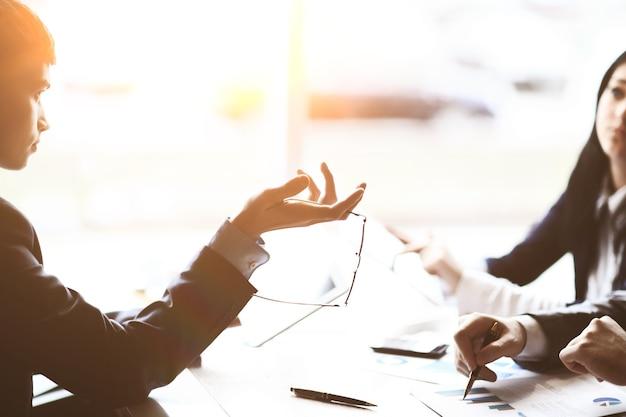 Размытое изображение бизнес-команды, говорящей за столом.