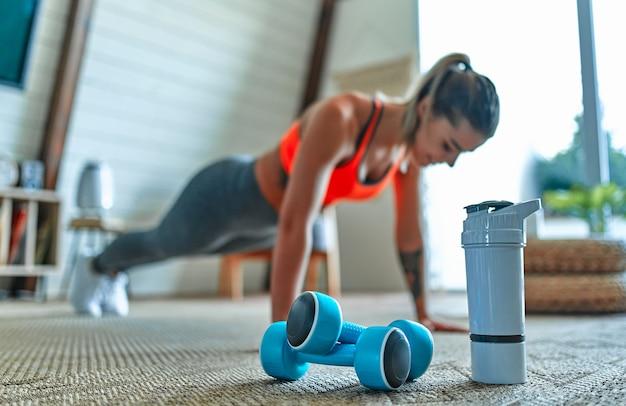 レギンスとトップの若い美しい運動少女のぼやけた画像は、自宅で運動板を作ります。健康的な生活様式。プロテインシェイクのボトルを持った前景のダンベル。