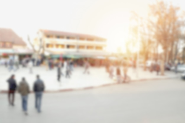 Blurred image of people walking across the street and crowd around the market in ifrane, morocco.