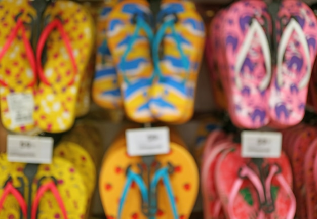 Blurred image of the row of vivid color beach sandals hanging on the rack