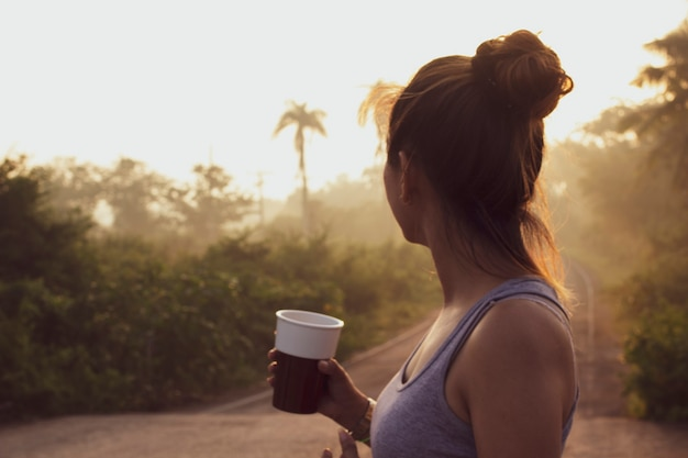 Blurred image of a woman holding a cup of coffee in the middle of nature.