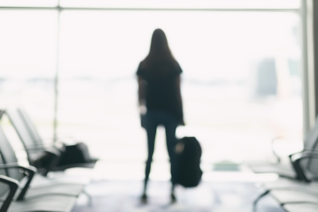 Blurred image of a woman traveler with backpack at the airport