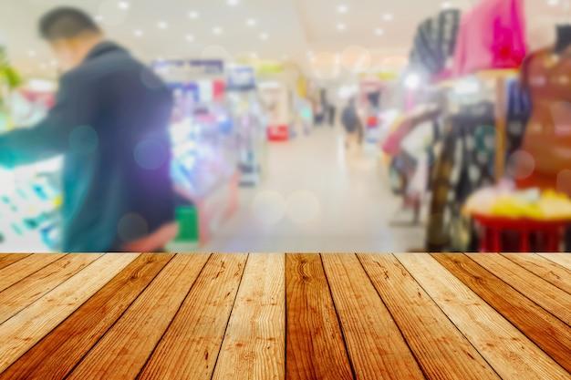 ぼんやりしたイメージの木製テーブルと抽象的なデパートショッピングモールセンターと人々の背景