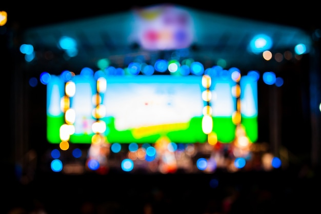 Blurred images of the concert stage full of bokeh lights at night.