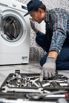 Blurred instruments working man plumber in bathroom near washing machine