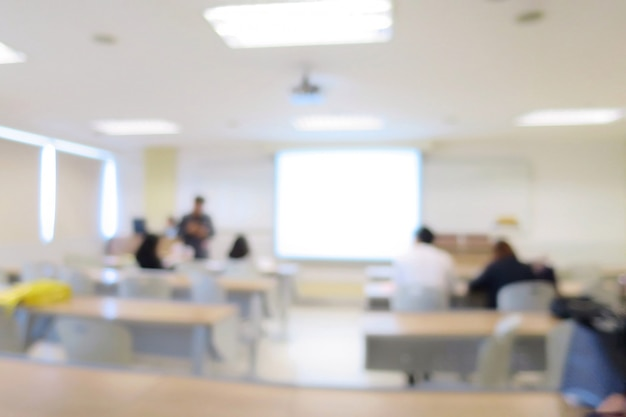 Blurred of lecture room or meeting room with long table, chairs, projector, and big window. education.