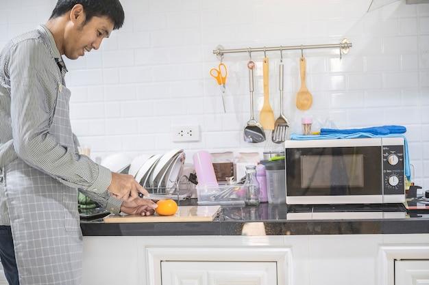 家の台所でアジア料理を調理するぼやけた男彼は野菜と果物を切る手