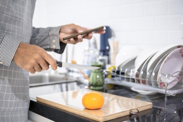 집의 부엌에서 흐리게 남자 아시아 요리 그는 야채를 절단 손