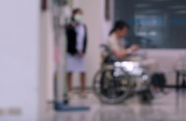 병원에서 치료를 기다리는 간호사와 휠체어에 흐리게 남자. 건강 관리 또는 가족 관계 개념.