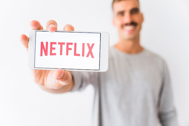 Blurred man showing smartphone with netflix writing