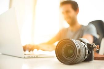 Blurred man using laptop behind dslr camera on desk