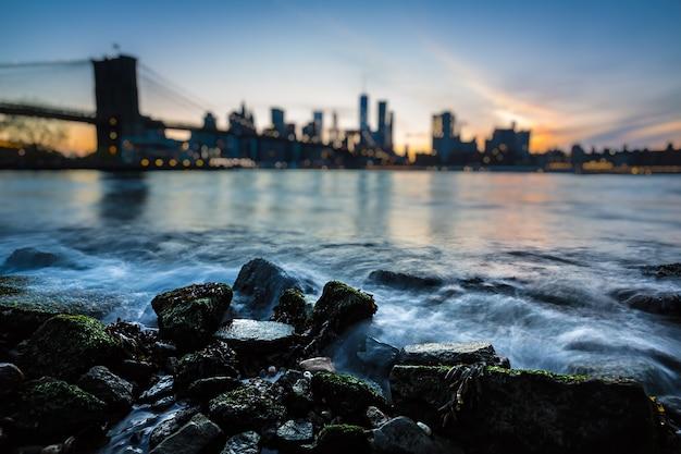 Размытый горизонт манхэттена с бруклинским мостом вечером. скалы и камни на берегу ист-ривер