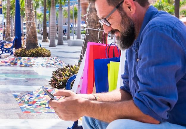 携帯電話を使用して、買い物をした後、ベンチで休んでいる黒ひげを持つぼやけた成熟した男