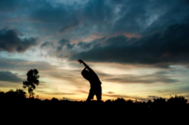 ぼんやりした動きシルエットの日の出のフィットネス男の運動welln