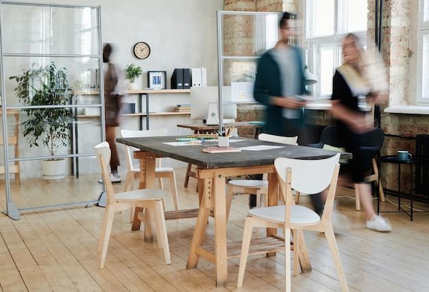 Размытые движения деловых людей, сотрудничающих в офисе, за столом для переговоров, стоящим в центре