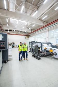 조명이 좋은 인쇄 공장의 현대 기계 사이에서 반사 조끼를 입은 작업자의 흐릿한 움직임