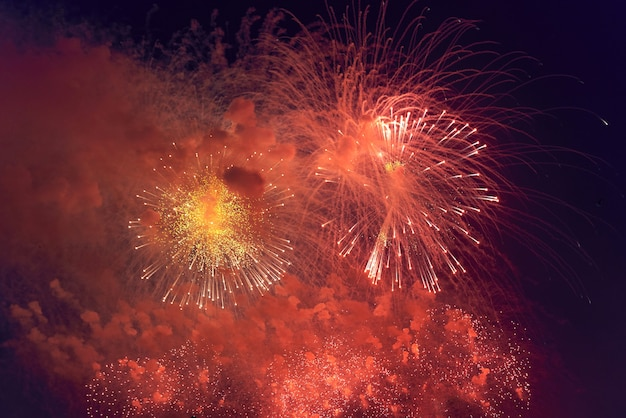 Blurred multicolored fireworks lights against the dark night sky