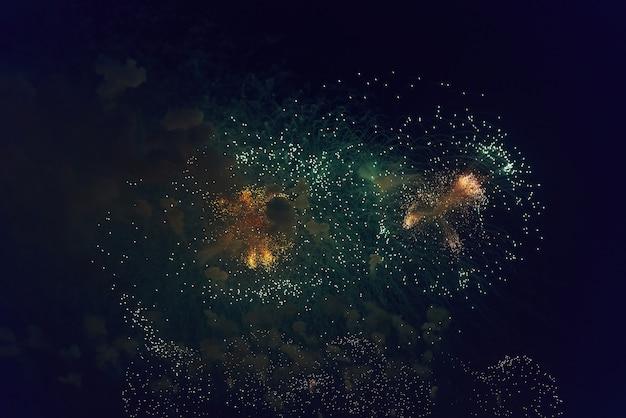 어두운 밤하늘을 배경으로 흐릿한 여러 가지 빛깔의 불꽃놀이