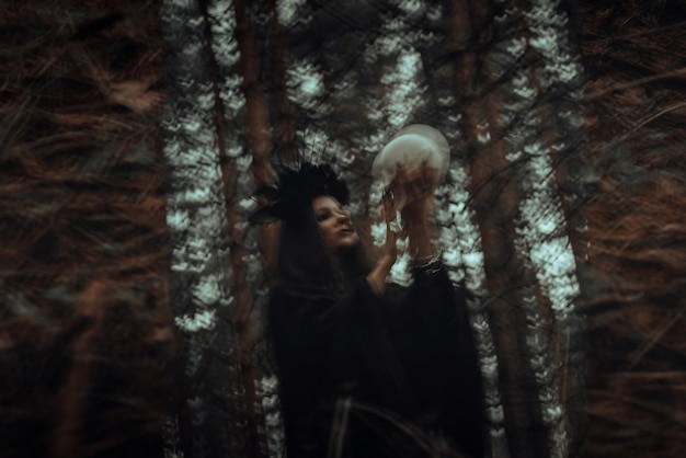 Blurred mystical reflection in the mirror of an evil scary witch with the skull of a dead man conjuring mystical occult rituals in forest