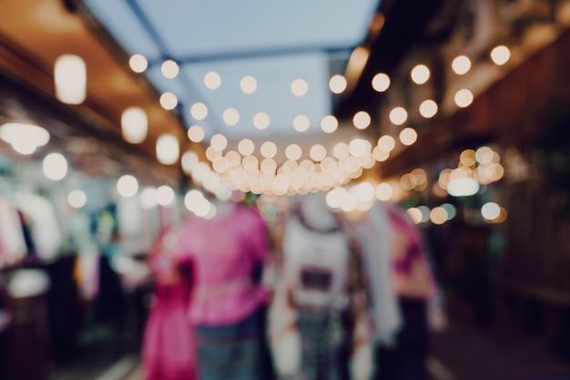 Blurred night market festival people walking on road
