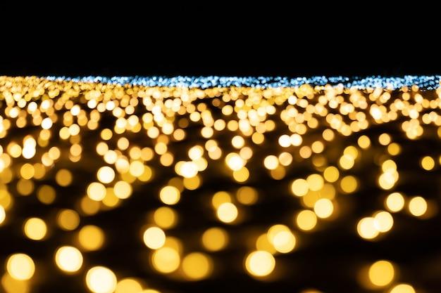 金と銀の電球がぼやけて背景を照らします。休日のお祭り。