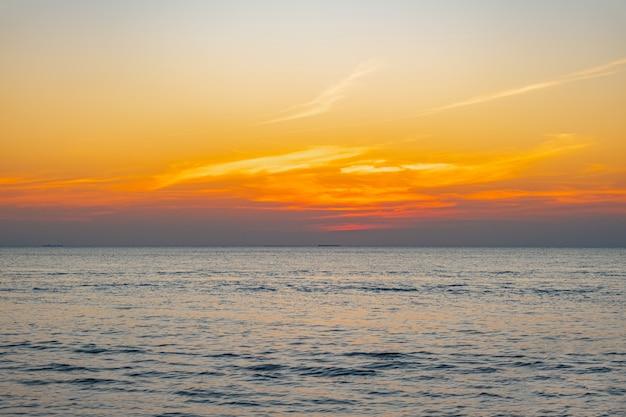 ビーチの海に沈む熱帯のカラフルな夕日のぼやけ。