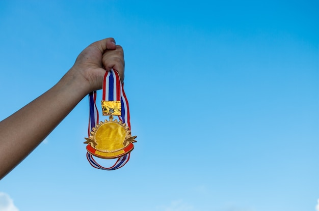 成功したスポーツやビジネス、勝者の成功賞のコンセプトを示すために、青い空の背景に対してタイのリボンで金メダルを持ち上げている女性の手のぼかし。