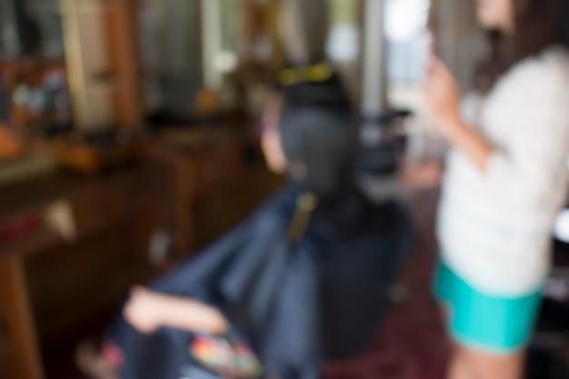 Размытая женщина в парикмахерской, делающая свой прическа