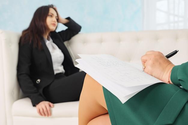 치료 세션에서 치료사와 이야기하는 소파에 앉아 있는 젊은 여성의 흐릿함, 심리학자에 대한 선택적 집중