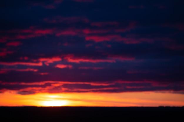 저녁 하늘에 석양에 의해 조명 흐릿한 주황색 보라색 극적인 구름
