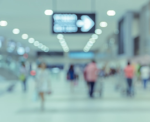 Blurred passengers in airport arrival terminal background
