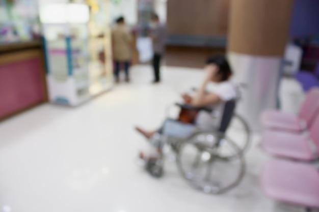 医者に行くのを待っている車椅子に座っているぼやけている患者